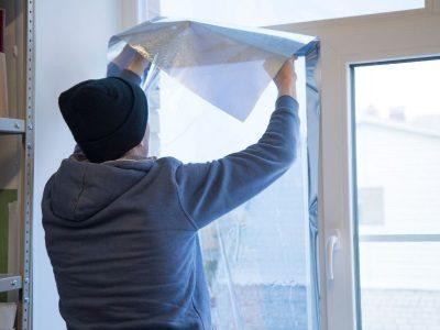 Guy putting up window film